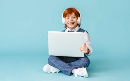 Photo pour Full body cheerful ginger boy smiling and looking at camera while doing homework project on laptop and sitting cross legged against blue background - image libre de droit