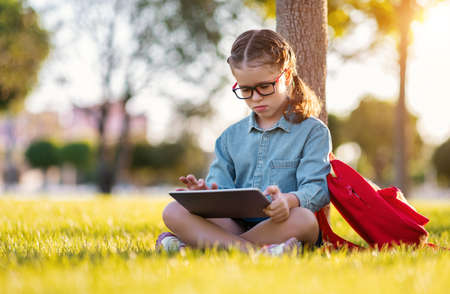 Photo pour Side view of happy girl in glasses smiling and reading notes in tablet pc while sitting on lawn near tree and doing homework in park - image libre de droit