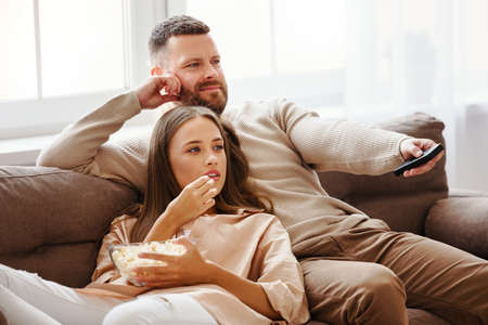 Photo pour Family couple watching television at home on the sofa - image libre de droit