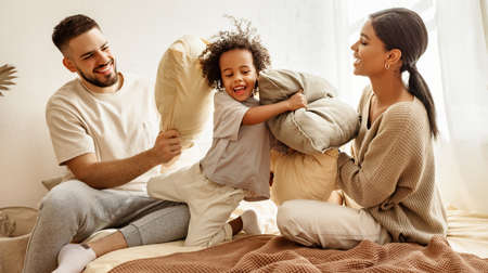 Photo for happy family multiethnic mother, father and son laughing, playing, fights pillows and jumping in bed in bedroom at home - Royalty Free Image