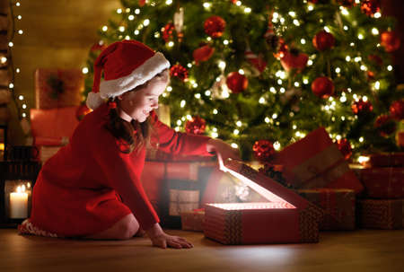 Photo pour happy laughing child girl with magic gift sitting in front of Christmas tree on Christmas Eve - image libre de droit