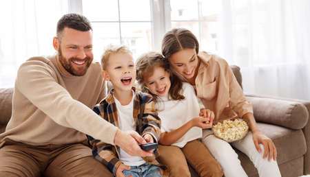 Photo for Delighted family parents and kids eating popcorn and laughing while sitting on sofa and watching funny movie at home - Royalty Free Image