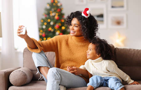 Photo for Happy ethnic african american family on holiday: happy mother taking selfie with child congratulating each other at Christmas in a cozy room at home - Royalty Free Image