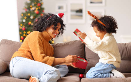 Photo for Happy family: ethnic woman sitting on sofa and opening gifts with boy in Santa hat together while celebrating Christmas at home - Royalty Free Image