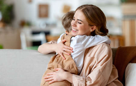 Photo pour Happy family: young woman and little boy in casual clothes embracing and kissing while congratulating on holiday mothers day in sunny room at home - image libre de droit