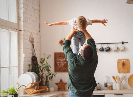 Photo pour Faceless carefree father in casual clothes lifting adorable little son above head while having fun together in contemporary kitchen - image libre de droit