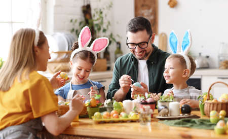 Photo pour Joyful family wearing bunny ears headbands gathering at table in modern light kitchen and paining Easter eggs together - image libre de droit