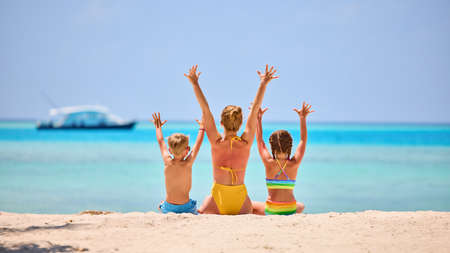 Photo pour Back view of woman with daughter and son in colorful swimsuits raising arms while sitting on sandy beach of exotic ocean shore - image libre de droit