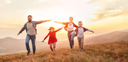 Photo pour Happy family: mother, father, children son and daughter running on nature on sunset - image libre de droit
