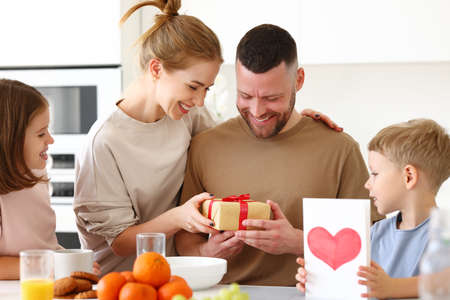 Photo for Surpise for daddy. Cute smiling children siblings giving father wrapped gift box and postcard. Young mom congratulating husband with kids while having breakfast in kitchen at home. Family holiday concept - Royalty Free Image
