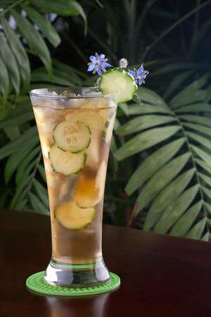 Closeup of glass of ginger and cucumber iced tea garnished with borage flowers on a table in a restaurant on a tropical beach.