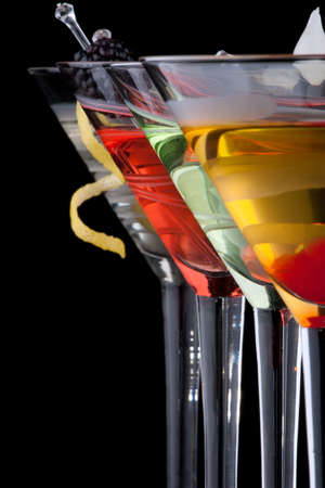 Classical martini in chilled glass over black background on reflection surface, garnished with freah blackberry, maraschino cherry, marinated pearl onoions, olive and lemon twist. Most popular cocktails series.