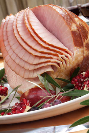 Dinning table set with glazed whole baked sliced ham, garnished with pomegranate, olives, and red pears