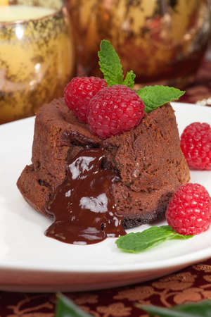 Delicious dark chocolate lava cake dessert served with fresh raspberries and mint  Surrounded by Christmas ornaments