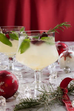 Close-up of white cranberry spritzer cocktail on holiday table with Christmas ornaments  Holiday cocktails series