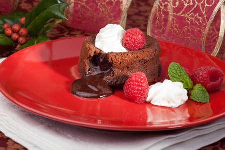 Delicious dark chocolate lava cake dessert served with fresh raspberries and mint. Surrounded by Christmas ornaments.