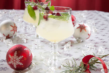 Close-up of white cranberry spritzer cocktail on holiday table with Christmas ornaments. Holiday cocktails series.