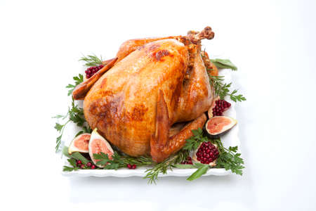 Photo pour Garnished traditional roasted turkey, garnished with fresh figs, pomegranate, and herbs. On white background. - image libre de droit
