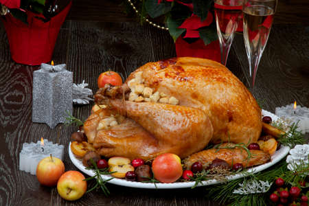 Photo pour Garnished roasted Christmas turkey with grab apples, sweet chestnut, cranberry, Christmas ornaments, candles, and pine cones. - image libre de droit