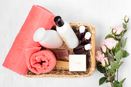 Towel cosmetics spa comb hair lotion candle flowers on white wooden background isolation