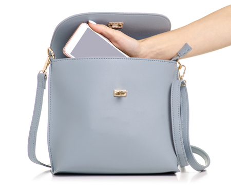 A hand put the phone in the female blue gray leather handbag on a white background isolation