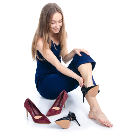 Photo for Woman sits chooses high heel shoes on white background. Isolation - Royalty Free Image