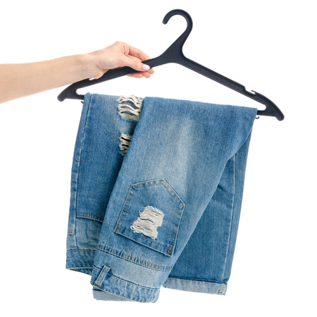 Photo pour Blue jeans on hanger in hand isolated on white background - image libre de droit