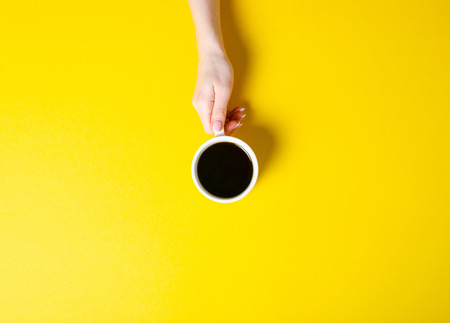 Photo pour Cup of coffee in hand on yellow background, top view - image libre de droit
