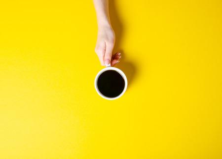 Foto de Cup of coffee in hand on yellow background, top view - Imagen libre de derechos