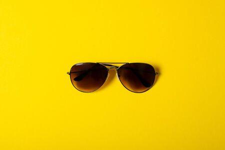 Photo pour Sunglasses fashion style on yellow background, top view - image libre de droit