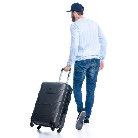 Photo pour Man in jeans with travel suitcase goes walking - image libre de droit