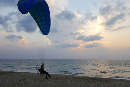 Silhouette of a male paraglider on a paraplan against a background of a sunset in the sky and clouds hovering over the sea. Concept: freedom, loneliness, hobby, sport.