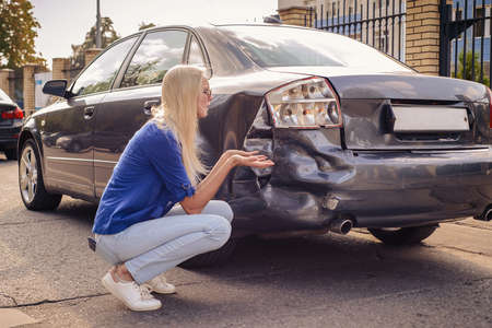 Photo pour The girl sits at the broken car and thinks what to do. - image libre de droit