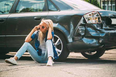 Photo pour girl sits on the road, near the broken car and calls on the phone, calling for help. - image libre de droit