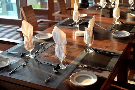 Foto de Empty glass with napkin and silverware on table for dinner setting - Imagen libre de derechos