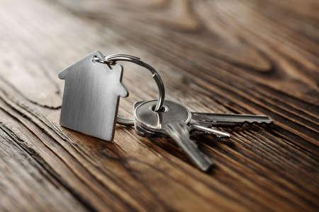Photo pour Symbol of house with silver key on wooden background - image libre de droit