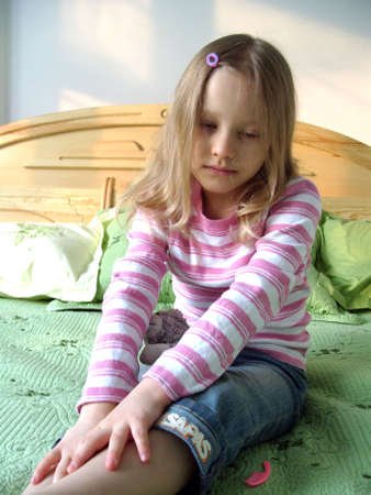 The little girl sitting on the bed. The little girl sitting on the bed, Young girl sitting on a bed, little sad crying girl sitting on the bed.