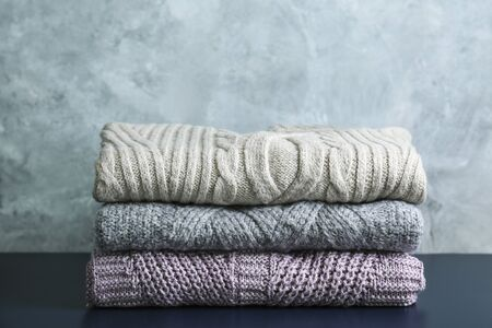 Photo pour Bunch of knitted warm pastel color sweaters with different knitting patterns folded in stack on brown wooden table, grunged texture wall background. Fall winter season knitwear. Close up, copy space - image libre de droit