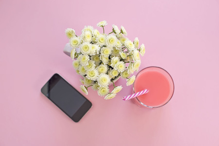 Bouquet of chrysanthemum flowers in a Cup of tea glass cocktail phone. Festival pink background top view Flat lay