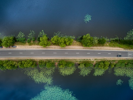 Landscape of an asphalt road. View from above on the road going along the blue river. Summer photography with bird's eye view.