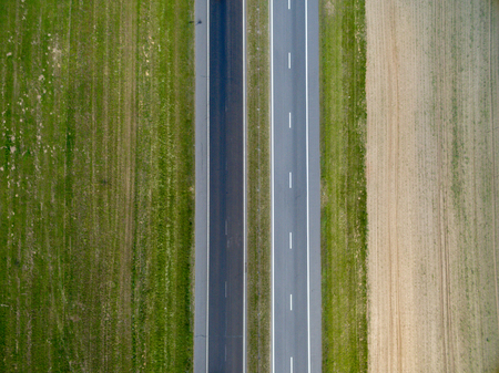 Photo pour Aerial top view of asphalt road through a green field in summer in Belarus. Nature from a bird's eye view - image libre de droit