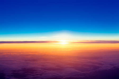 Photo for sunset with a height of 10 000 km  Dramatic sunset  View of sunset above clouds from airplane window - Royalty Free Image