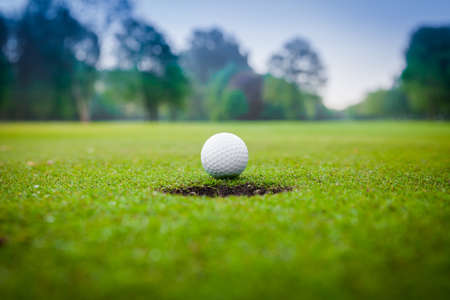 Photo for Golf ball on green meadow. golf ball on lip of cup  - Royalty Free Image
