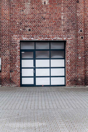Large garage door with brick wall and asphalt driveway