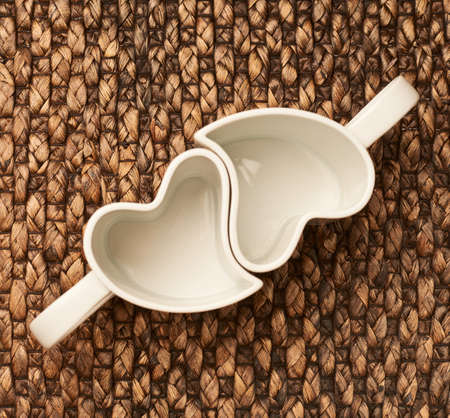 Paired heart shaped empty cups over the brown wicker surface, view above