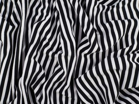 Fragment of a striped wrinkled black and white piece of a cloth fabric as a background texture