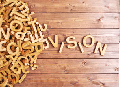 Photo pour Word vision made with block wooden letters next to a pile of other letters over the wooden board surface composition - image libre de droit