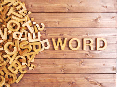 Photo pour Word word made with block wooden letters next to a pile of other letters over the wooden board surface composition - image libre de droit