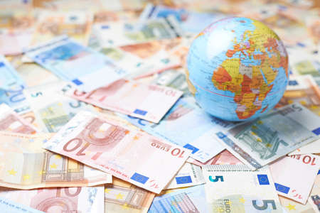 Photo pour Tiny Earth globe over the surface covered with the multiple bank note bills - image libre de droit