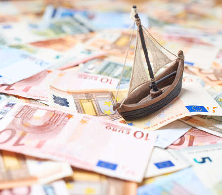 Tiny ship over the surface covered with the multiple euro bank notes, shallow depth of field composition